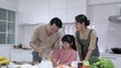 Asian family make smoothie together in kitchen at home. Little girl with father and mother make drink refreshment. Concept of happy family and activity holiday.