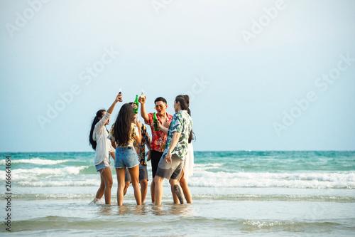 Fototapeta A group of friends who party and play fun on the beach. obraz na płótnie