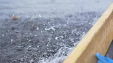 Motion Blur Of Water Spray Coming Off The Side Of Wooden Boat (slow Motion)