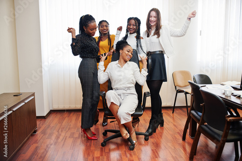 Fényképezés  Five multiracial business womans standing at office and roll woman on chair