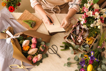 Florist Writing In Notebook At Table