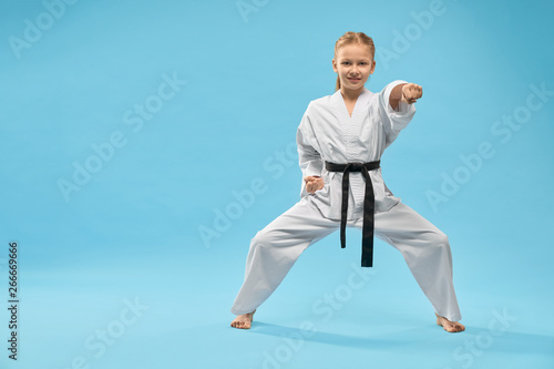 Photo Female teenager standing in stance and punching in studio
