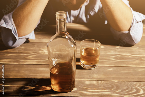 Cadres-photo bureau Bar Alcoholic addict. Man near the table with alcohol and a glass. Dangerous habit. Unhealthy life concept. Social problem.