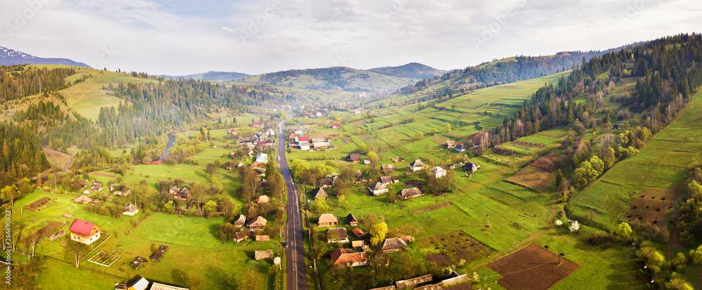 Fototapeta Road in mountain village. Aerial Panorama of Carpathian valley.