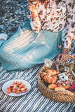 Fototapeta Coffie - Summer beach picnic at sunset. Young couple having weekend picnic outdoors at seaside with fresh fruit, tray of tasty appetizers and sparkling wine