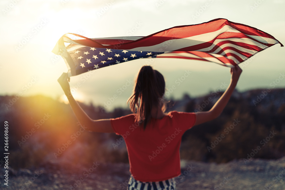 Fototapety, obrazy: Child girl is waving American flag on top of mountain at sky background. Sunset time