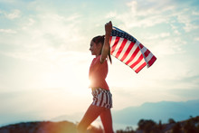 Child Girl Is Running With USA American Flag At Sunset
