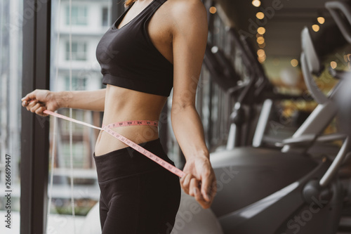 Obraz Closeup woman slim athlete using body fat measurement and waist size with waist line after workout at fitness gym healthy lifestyle weightloss happy in goal. - fototapety do salonu