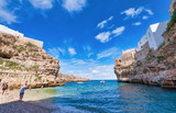 POLIGNANO A MARE, ITALY - SEPTEMBER 16, 2014: People enjoy city beach on a beautiful summer day. The city is a famous tourist attraction in Apulia - 266700422