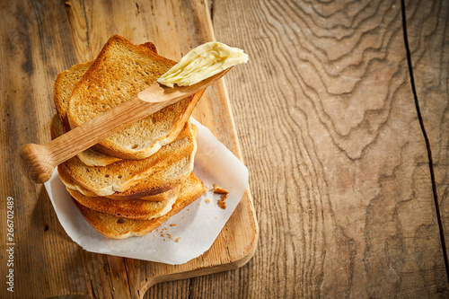 Wooden butter spreader on a stack of toast