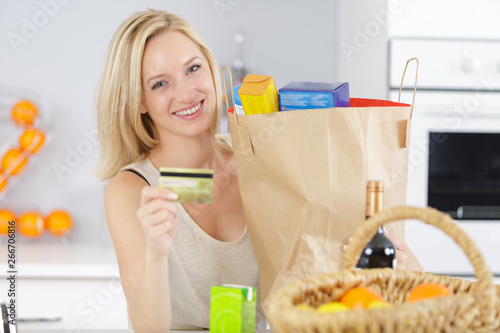 Poster de jardin Individuel woman in the kitchen with grocery bags showing bank card