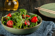 Salad with tomatoes, arugula and spinach on a black wooden table