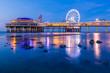 Colorful blue hour sunset on coastline, beach, pier and ferris wheel, Scheveningen, the Hague.