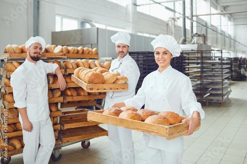 Staande foto Bakkerij Bakers hold a tray with fresh bread in the bakery.