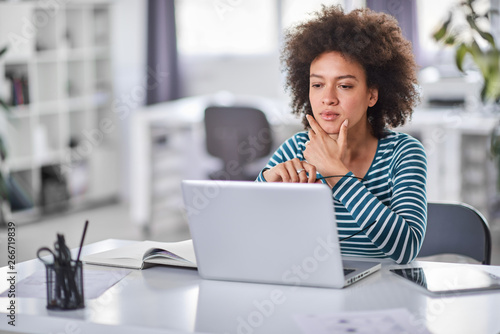Fotografía  Cute mixed race businesswoman dressed  casual thinking how to solve a problem while sitting in modern office