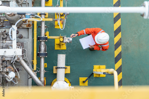 Fotografía Oil and gas industry activity, operator check and inspect oil pump differential gauge and pressure transmitter as daily log sheet record for monitor production process