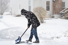Young Man In Winter Coat Cleaning Shoveling Driveway Street From Snow In Heavy Snowing Snowstorm With Shovel By Residential House And Snowflakes Falling