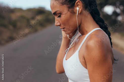 Sportswoman taking break and listening music - 266728272