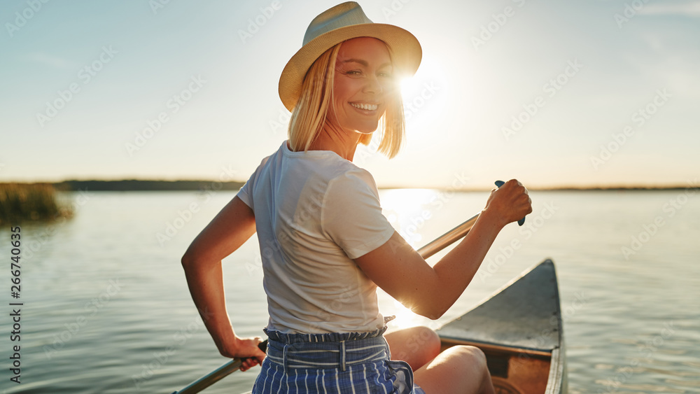 Fototapeta Smiling woman paddling her canoe on a lake in summer
