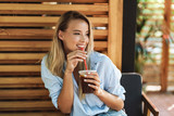 Smiling young woman drinking juice while sitting at the cafe