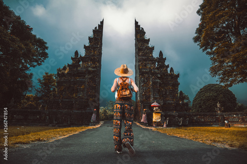Tourist woman with backpack at vacation walking through the Hindu temple in Bali in Indonesia
