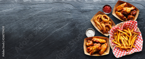 Fototapeta pub appetizers such as chicken wings, onion rings and french fries in panoramic composition obraz
