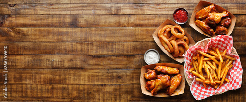 Vászonkép pub appetizers such as chicken wings, onion rings and french fries in panoramic