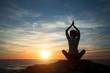 Leinwandbild Motiv Silhouette young woman practicing yoga on the beach at amazing sunset.