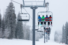 Skiers Ascend The Chairlift To...