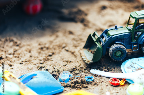 Photo  Summer Children's Toys on the sand, sand box, green tractor