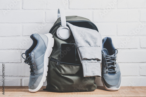 Fotografía  Green backpack with sportswear and sneakers