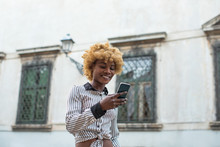 Young Black Stylish Woman Walking On The City Street  With A Smartphone