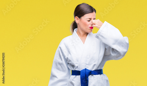 Fotografie, Tablou  Young beautiful woman wearing karate kimono uniform over isolated background smelling something stinky and disgusting, intolerable smell, holding breath with fingers on nose