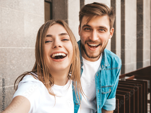 Obraz Smiling beautiful girl and her handsome boyfriend in casual summer clothes. Happy family taking selfie self portrait of themselves on smartphone camera. Having fun on the street background - fototapety do salonu