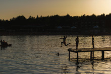 People Jump From The Pier Into Lake Issyk Kul. Guys Swim In The Lake At Sunset. The Texture Of The Surface Of The Water. Rest In Kyrgyzstan.