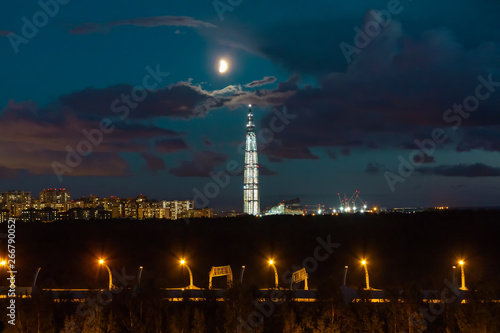 night cityscape. View of the Lakhta Center tower in St. Petersburg in the sunset with clouds and moon