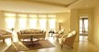 Backward shot of luxury modern apartment interior design natural lighting with colorful flowerpot and chandelier and Persian carpet, candlestick and beige sofa and ,orchid dining table