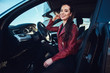 Leinwandbild Motiv Happy young woman is sitting in her new car. She is wearing red leather jacket.