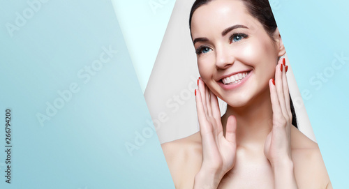 Fototapeta  Beautiful young woman with perfect glow smooth clean skin touching her face