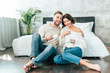 Leinwandbild Motiv handsome man hugging beautiful woman and sitting on floor with cup