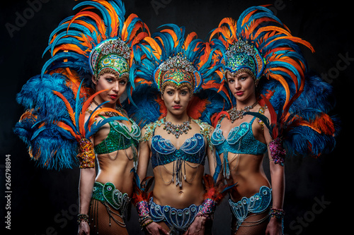 Foto op Canvas Carnaval Portrait of a group sexy dancers female in colorful sumptuous carnival feather suits. Isolated on a dark background.