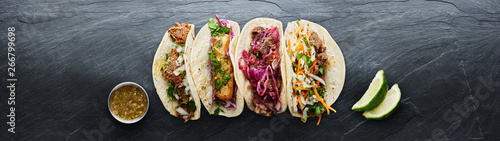 Fototapeta four mexican street tacos with fish barbacoa and carnitas shot in panoramic composition obraz