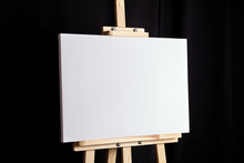 White Blank Canvas Stands On A Wooden Artistic Easel On Black Curtain Background. Horizontal Rectangular Mockup Canvas Wrapped On Stretcher Bar