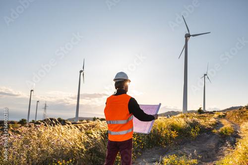 Photo Giovane ingegnere con gilet ad alta visibilità, casco bianco e progetto in mano, sta controllando l'impianto eolico formato da turbine a vento in montagna
