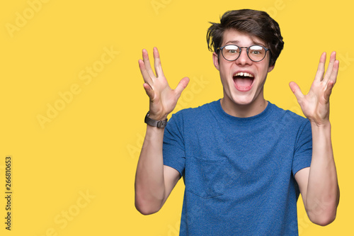 Fotografía Young handsome man wearing glasses over isolated background celebrating crazy and amazed for success with arms raised and open eyes screaming excited
