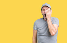 Handsome Middle Age Hoary Senior Man Wearing Sport Cap Over Isolated Background Yawning Tired Covering Half Face, Eye And Mouth With Hand. Face Hurts In Pain.