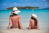 Mother and daughter talking on a beautiful beach, sitting on the water edge, view from the back - 266815693