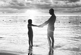 Father and daughter silhouettes at sunset on the beach - 266815809