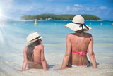 Mother and daughter talking on a beautiful beach, sitting on the water edge, view from the back - 266816484