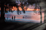 Silhouettes of people walking on the beach at dusk - 266816817